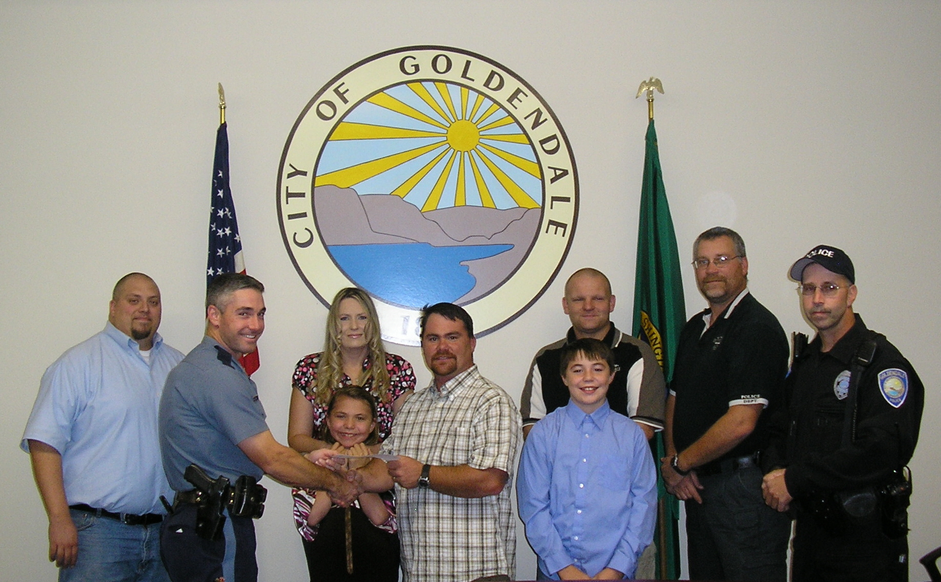 Senior Trooper Holloran of The Oregon State Police presents Brandon Walter with a check for $8713. The check was given to the family at the Goldendale Police Department.
