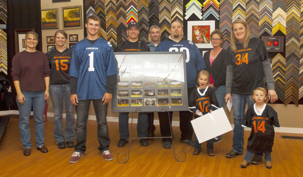 Pig Bowl Board membes Jennifer Holloran, Melissa Wykes, Randy Wells, Michael Holloran, Curt Harth and Tammy Keys stand with Donovan and Kadee alongside the beautiful frame of event photos created and donatated by Marty Hiser of Westwind Frame and Gallery.